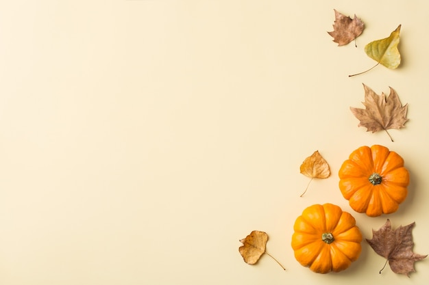 Composizione del giorno del ringraziamento autunnale con zucche arancioni decorative e foglie secche. lay piatto, vista dall'alto, copia spazio, sfondo giallo natura morta per biglietto di auguri