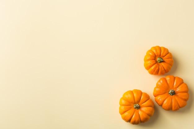 Composizione del giorno del ringraziamento autunnale autunnale con zucche arancioni decorative. disposizione piana, vista dall'alto, copia spazio, sfondo giallo natura morta per biglietto di auguri