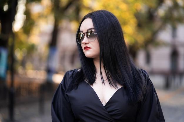 Moda autunno. la ragazza con le labbra rosse in elegante abito nero alla moda e occhiali da sole, stile di vita sullo sfondo di alberi sfocati verde giallo nel parco.