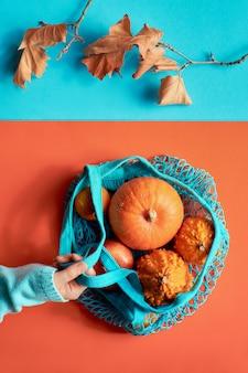 Autunno piatto disteso, mano in maglione blu che tiene un sacchetto di stringa turchese con zucche arancioni su carta divisa abbinata