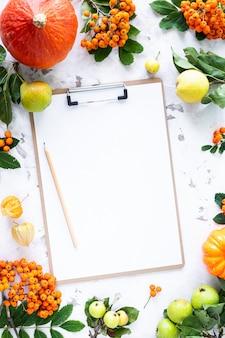 Piatto autunnale con un foglio di carta bianco per scrivere. copia spazio, vista dall'alto. modello