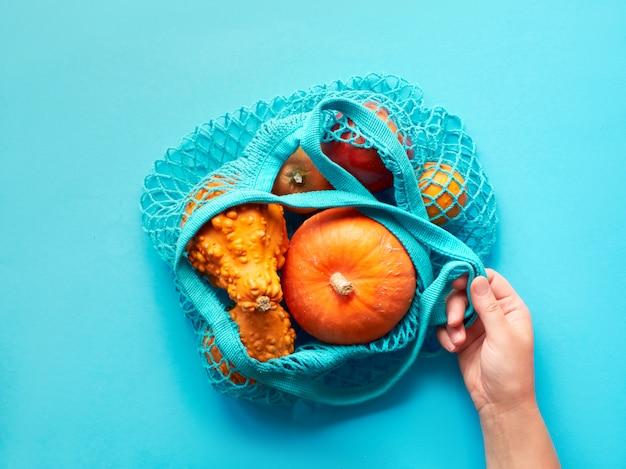 Autunno piatto disteso con mano femminile che tiene la borsa di stringa turchese con zucche arancioni su carta blu menta