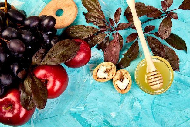 Autunno cibo natura morta con frutta stagione uva, mele rosse e fichi su un tavolo blu.