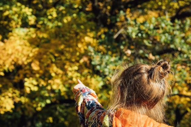 Bosco autunnale. vista posteriore della ragazza che punta il dito su alberi verdi e gialli sfocati.
