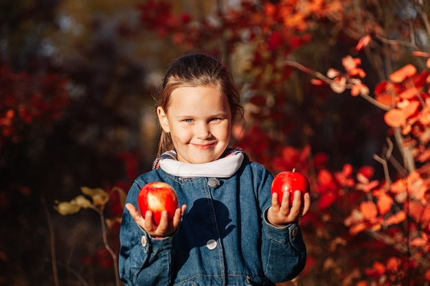 Concetto di foresta autunnale ragazza felice e carina in cappotto di jeans tiene una grande mela rossa con sfondo autunnale
