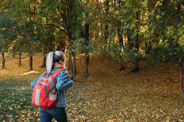 Escursionismo nella foresta d'autunno. vista posteriore della signora che viaggia con lo zaino nel parco naturale.