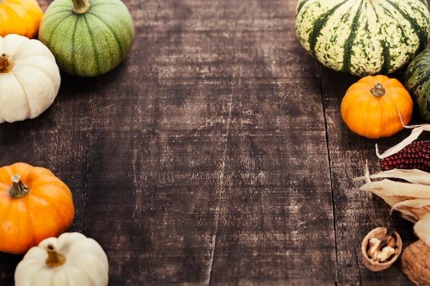 Cornice autunnale da zucche e mais sul vecchio tavolo in legno. concetto di giorno del ringraziamento