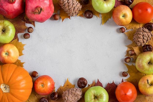 Cornice autunnale con frutti autunnali su sfondo grigio cemento piatto con spazio di copia