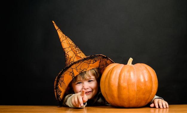Costume da strega autunno festa di halloween ottobre ragazzo sorridente in cappello da strega con zucca di halloween