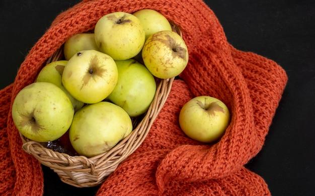 Raccolto autunnale. concetto di caduta. mele gialle in un cestino. sfondo scuro. messa a fuoco selettiva. vista dall'alto.