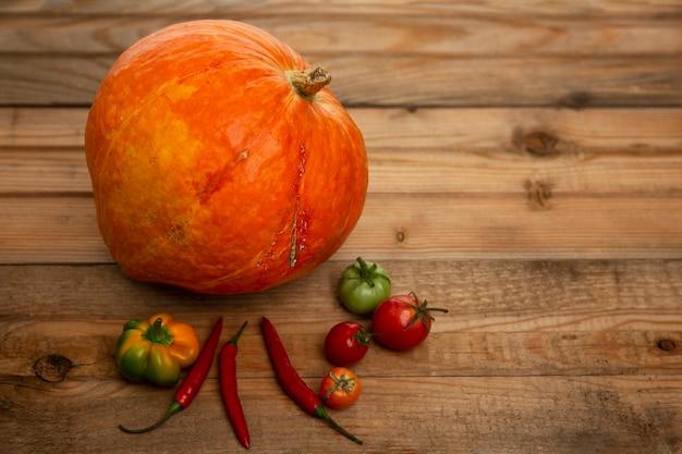 Raccolto autunnale di frutta e verdura su una tavola di legno. zucca, melone, zucchine, pomodori, mele e peperoni. vitamine dalla natura. vista dall'alto. spazio per il testo.