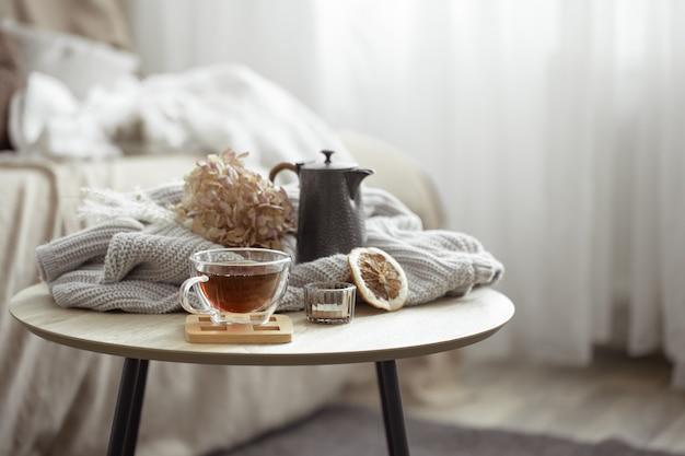 Composizione domestica autunnale con una tazza di tè, una teiera e un elemento a maglia.