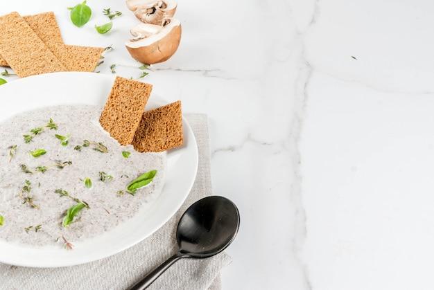 Piatti caldi autunnali. zuppe vegane vellutata di funghi con champignon ed erbe marroni fritti, timo. su un tavolo di marmo bianco.