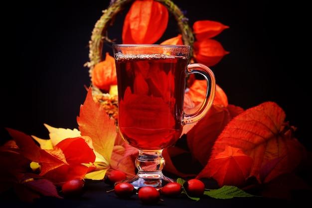 Bevanda calda autunnale con rosa selvatica su fondo di legno in stile rustico retrò physalis in un cestino