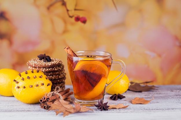 Tè caldo autunnale con limone e spezie in tazza di vetro. tè sano con biscotti, limoni e foglie intorno. concetto di autunno