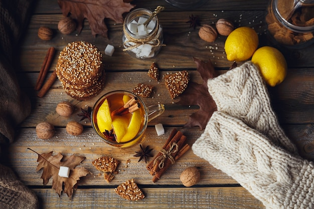 Tè caldo autunnale con limone e spezie in tazza di vetro. tè sano con biscotti, noci e foglie intorno. concetto di autunno