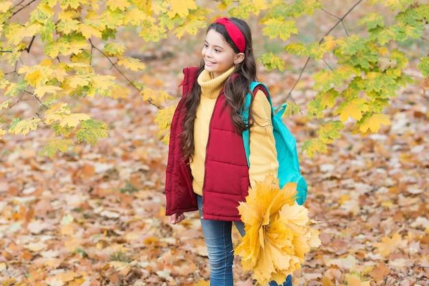 Moda bambino autunnale. stagione romantica per l'ispirazione. infanzia felice. di nuovo a scuola. adolescente con le foglie di acero della tenuta dello zaino nel parco. bellezza della stagione autunnale. goditi la giornata nella foresta. seguimi.