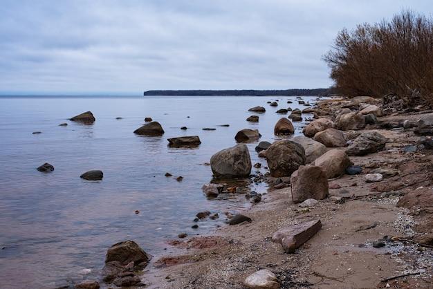 Paesaggio autunnale sul bacino idrico di rybinsk, russia. spiaggia di sabbia con alberi e rocce. cielo nuvoloso