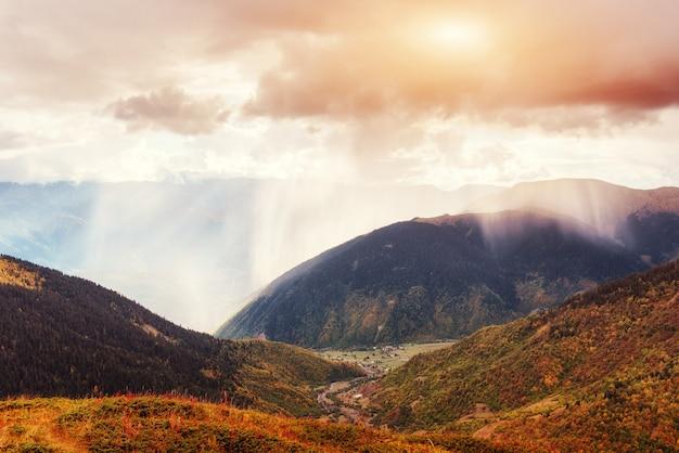 Paesaggio autunnale e cime innevate al sole.