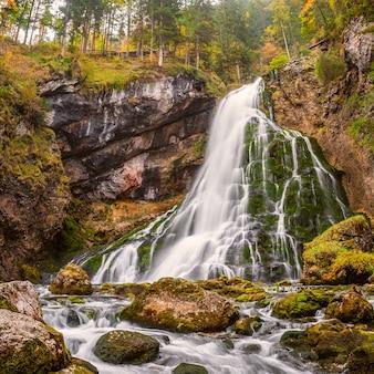 Paesaggio autunnale con bella cascata in montagna