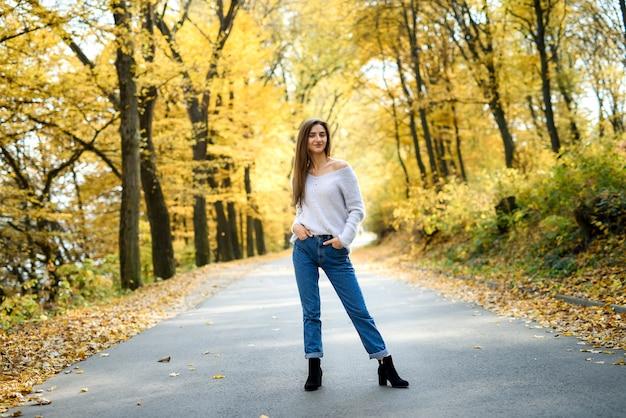 Paesaggio autunnale. donna in abbigliamento casual in posa nel parco con foglie gialle