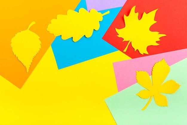 Foglia d'autunno ritagliata di carta gialla su sfondo di carta colorata
