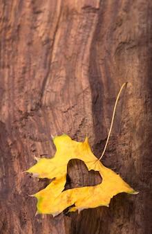 Foglie d'autunno. cuore di foglie d'autunno. foglie di autunno sulla superficie del legno