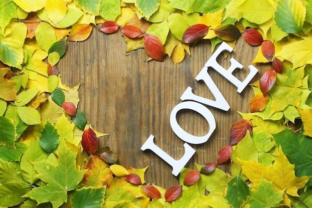 Fondo delle foglie di autunno a forma di cuore sulla tavola di legno