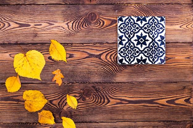 Bordo di foglie di autunno e piastrelle con ornamento sullo sfondo di legno vecchio