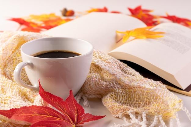 Foglie di autunno, tazza di caffè, sciarpa calda di lettura del libro e libro aperto sul tavolo. messa a fuoco selettiva.