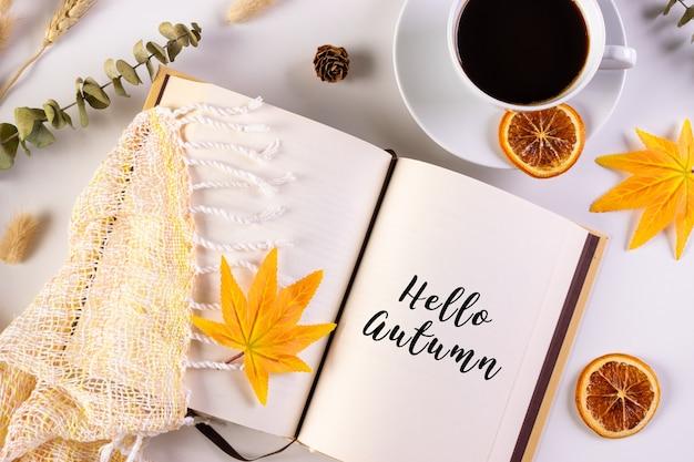 Foglie di autunno, tazza di caffè e libro aperto sul tavolo con testo hello autumn. autunno o autunno.