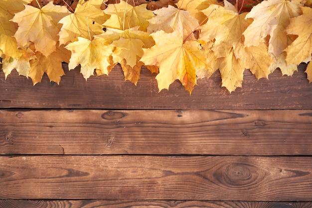 Cornice di foglie di autunno sulla vista superiore del fondo di legno tavolo in legno vintage di foglie gialle e arancioni del confine di caduta