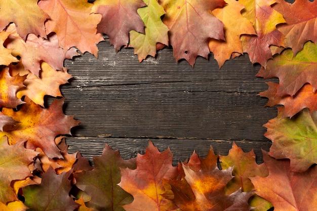 Foglie di autunno sul fondo della tavola in legno cornice di autunno.