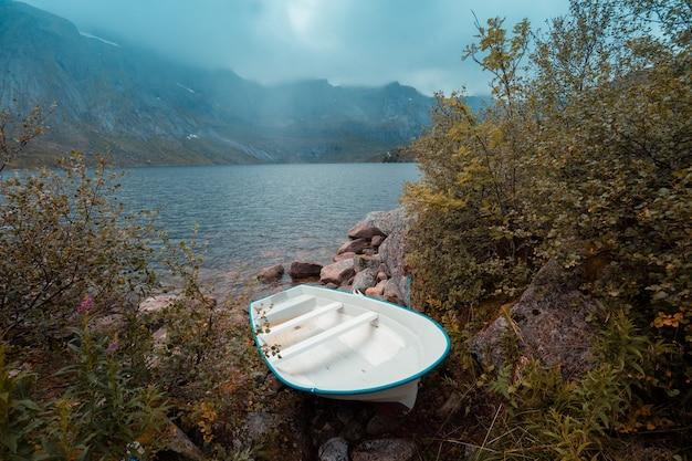 Mattina nebbiosa autunnale. barca in riva al lago. bellissimo guado, norvegia