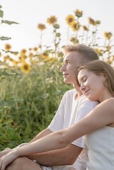 Natura autunnale. divertimento e bugie. giovane coppia di adolescenti che fa picnic sul campo di girasoli al tramonto, si diverte a guardare, donna sdraiata sulla spalla del fidanzato