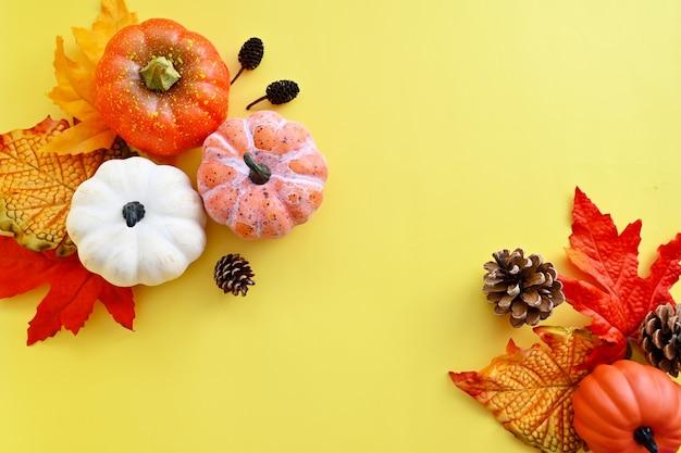 Foglie d'arancio autunnali, cornice astratta autunnale con foglie colorate, pigne e zucche su sfondo luminoso, copia spazio.