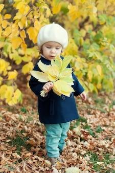Ritratto all'aperto di autunno di bella ragazza felice del bambino che cammina nel parco o nella foresta in sciarpa lavorata a maglia calda