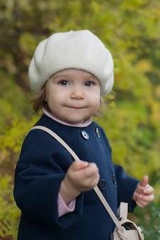 Ritratto all'aperto di autunno della ragazza bella bambino felice che cammina nel parco o foresta in sciarpa lavorata a maglia calda