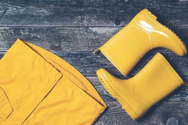Completo autunnale per bambini. disposizione piana, vista dall'alto. stivali da pioggia gialli e impermeabile. moda autunnale. stivali di gomma alla moda e cappotto su fondo di legno. impermeabile e stivali per bambini.
