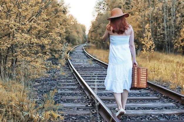 Ragazza del parco autunnale con un prendisole bianco e una valigia di vimini che cammina sui binari