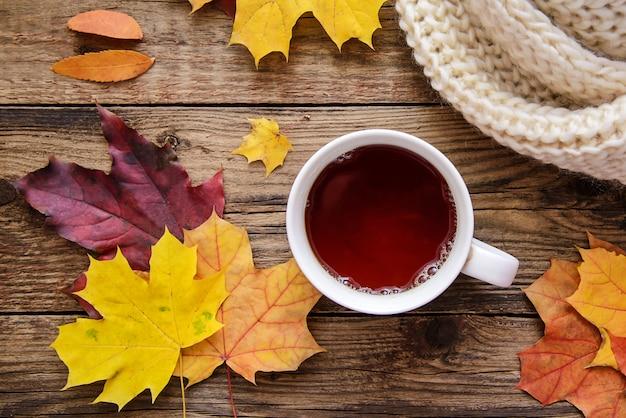 Maschera di autunno delle foglie gialle, una tazza di tè, una sciarpa e un pezzo di carta con la penna su fondo di legno
