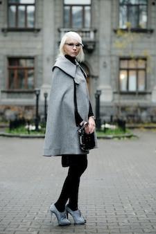 Ritratto autunnale di bella donna bionda in cappotto grigio con borsa nera