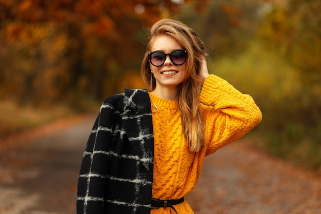 Ritratto autunnale di una bella ragazza con una faccia sorridente caucasica in un maglione lavorato a maglia vintage e un cappotto nero con occhiali da sole passeggiate nella natura. modello femminile in una giornata autunnale con fogliame giallo