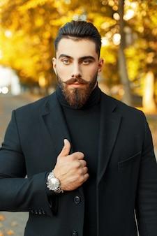Ritratto di autunno di un uomo hipster con barba e baffi in un elegante cappotto nero e un orologio in una giornata di sole
