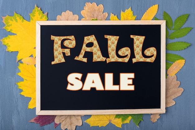 Concetto di vendita autunnale. cornice nera con la scritta fall sale su sfondo con foglie autunnali su fondo in legno blu.
