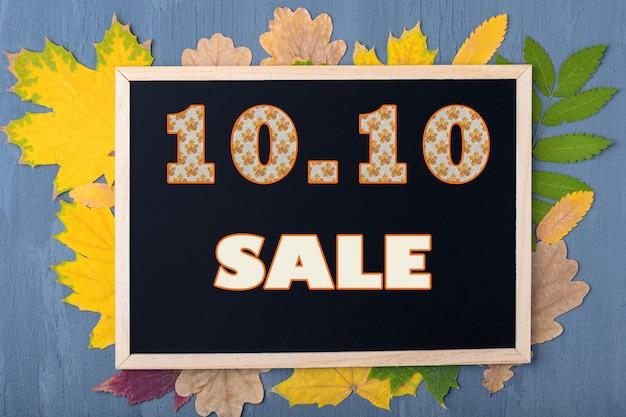 Concetto di vendita autunnale. concetto di venerdì nero. data 10 ottobre. calendario dei saldi autunnali. cornice nera con la scritta 10.10 sale su uno sfondo con foglie autunnali su fondo in legno blu.