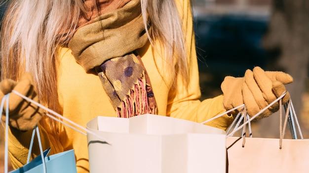 Saldi autunnali ritagliata colpo di signora che esamina le borse della spesa, controllando gli articoli acquistati