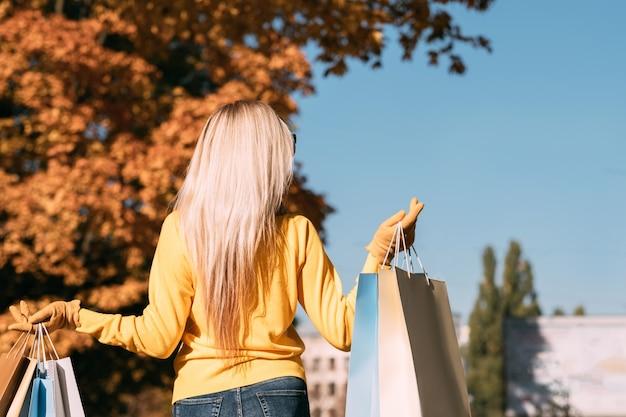 Nuova collezione stagione autunnale vista posteriore della signora che cammina con le borse della spesa