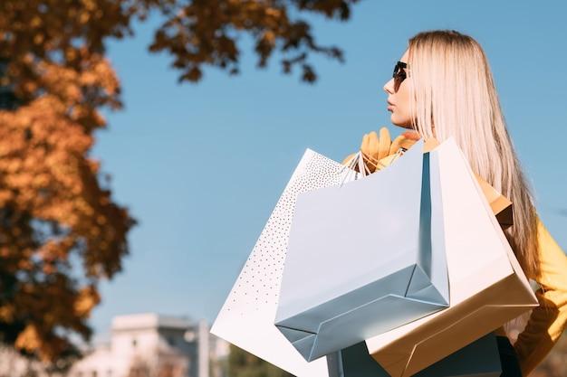 Nuova collezione stagione autunnale vista laterale della signora in piedi con le borse della spesa