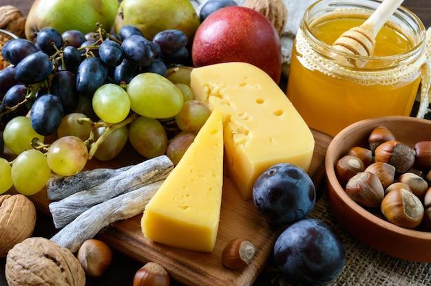 Set autunnale di prodotti uva noci prugne miele formaggio pere frutta secca su tavola di legno